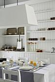 Esszimmer mit weißem Einbauschrank, einem gedeckten Tisch für vier Personen und einer großen Hängelampe darüber