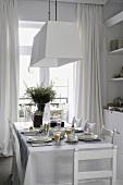 Gedeckter Esstisch mit blauen Tischläufern und weißem Geschirr vor dem Esszimmerfenster