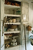 An open wooden cupboard containing crockery
