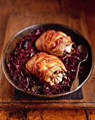 Bacon-wrapped quails on red cabbage