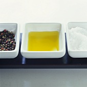 Peppercorns, oil and sea salt in three dishes