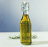 A bottle of olive oil with rosemary