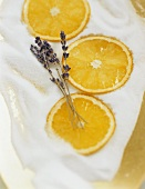 Slices of orange and lavender flowers on sugar