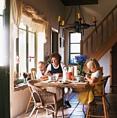 A mother and two children having breakfast in a country house living room
