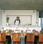 Frau bereitet Essen in offener Küche zu, gedeckter Tisch im Vordergrund