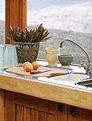 Kitchen utensils on draining board below window