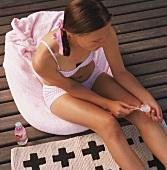Mädchen pflegt sich die Nägel auf der Terrasse