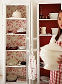 Woman holding soup tureen in front of dresser
