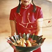 Frau hält Schale mit Keksen