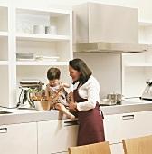 Mutter und Tochter in der Küche, Kind spielt mit Kochlöffeln