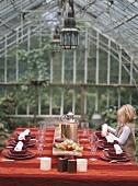 Kleines Mädchen deckt einen Tisch im Gewächshaus