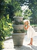 Kleines Mädchen versteckt sich im Garten hinter Blumentöpfen