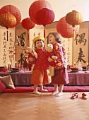 Zwei Mädchen spielen vor asiatisch gedecktem Tisch