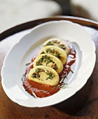 Semolina roulade with kale filling on tomato sauce