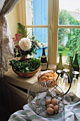 Eggs in wire basket, bread and flowers in front of kitchen window