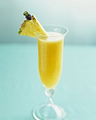 A champagne cocktail with mango and pineapple