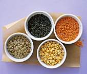 Different types of lentils & split peas in four small bowls