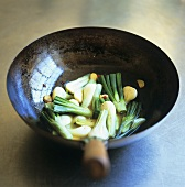 Spring onions, garlic and chilli in a wok