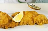 Sprinkling Wiener schnitzel (breaded veal escalopes) with oil