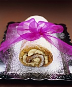 Poppy seed and cinnamon sponge roulade with icing sugar and pink bow