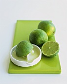 Limes with citrus squeezer on green chopping board