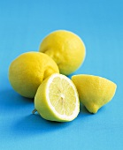 Two whole lemons and one halved lemon against blue background