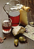 Red wine in glass and carafe, bread, cheese and olives