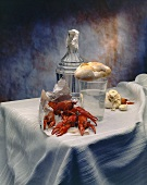 Crayfish, carafe and glass of water, bread and garlic on table