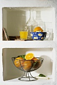 Orange juice, citrus squeezer and basket of oranges in wall niche