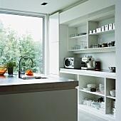 Durch das raumhohe Panoramafenster fällt viel Tageslicht in die moderne, weisse Küche