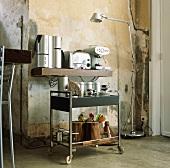 Moderne Küchengeräte auf einem schlichten Wandboard und einem Rollwagen vor einer alten Wand