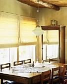 Alter Holztisch mit Stühlen und ein Spiegelschrank im Esszimmer eines rustikalen Wohnhauses