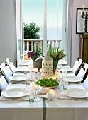 Ein sommerlich gedeckter Esstisch mit schöner Aussicht durch die Balkontür