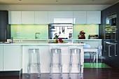 Eine Designerküche mit transparenten Barhockern aus Plexiglas