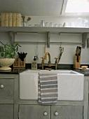 Großes Vintagespülbecken in einer grauen Holzküchenzeile