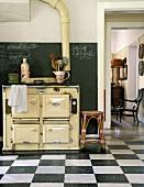 Ein antiker Holzofen in der Küche mit Schachbrettboden