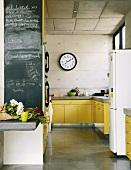 Leuchtend gelbe Küchentheken werten die rohen Betonwände der Küche auf