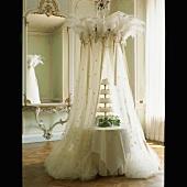 Eine romantisch inszenierte Hochzeitstorte mit federbekröntem Betthimmel aus Tüll