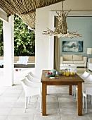 Ausgefallener Kronleuchter aus Ästen über einem einfachen Terrassentisch mit weissen Schalenstühlen