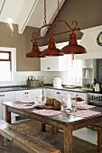 Ein rustikaler Holztisch mit Sitzbänken in einer klassischen Landhausküche mit Dachschräge