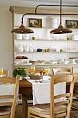Ein gemütlicher Frühstückstisch und ein großer Buffetschrank aus Holz, über dem Esstisch eine antike Metallleuchte mit mehreren Schirmen