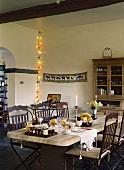 Ein massiver Esstisch aus Metall und Stein im Esszimmer mit rustikaler Holzbalkendecke