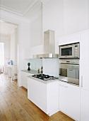 Einbaugeräte aus Edelstahl in einer weissen Designerküche im großzügigen, offenen Wohnraum mit Dielenboden und Stuckdecke