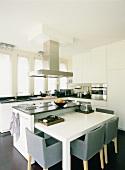 In der weissen Designerküche fügt sich ein minimalistischer Esstisch in den Küchenblock ein