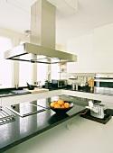 Eine moderne Designereinbauküche mit Granitoberflächen und Edelstahlelementen