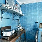 Der antike Wandtisch im komplett blau verfliesten Küchenraum dient als Kochtheke