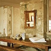 Antiker, rustikaler Holztisch und Spiegel vor einer alten, abgenutzten Wand