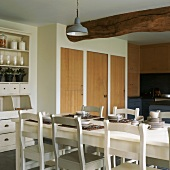 Durch die Decke des in klassischem Weiss eingerichteten Esszimmers verläuft ein massiver Holzbalken