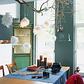 Eine selbstgebaute Hängeleuchte aus Zweigen und Federbällen über einem Esstisch mit Läufern, Kerzen und Tonschalen