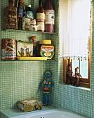 Witzige Verpackungsattrappen aus Pappmaschee auf Glasregalen im grün gefliesten Badezimmer